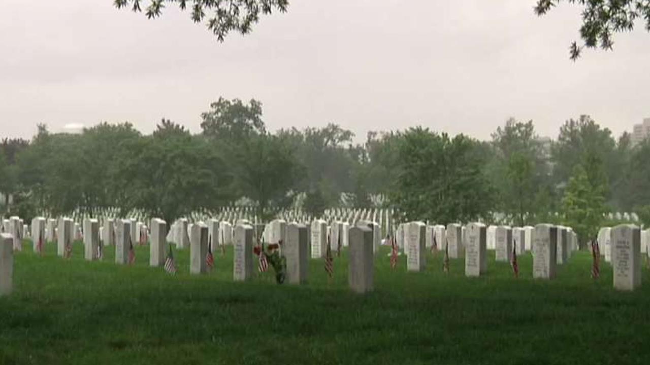 Volunteers place roses at Arlington headstones