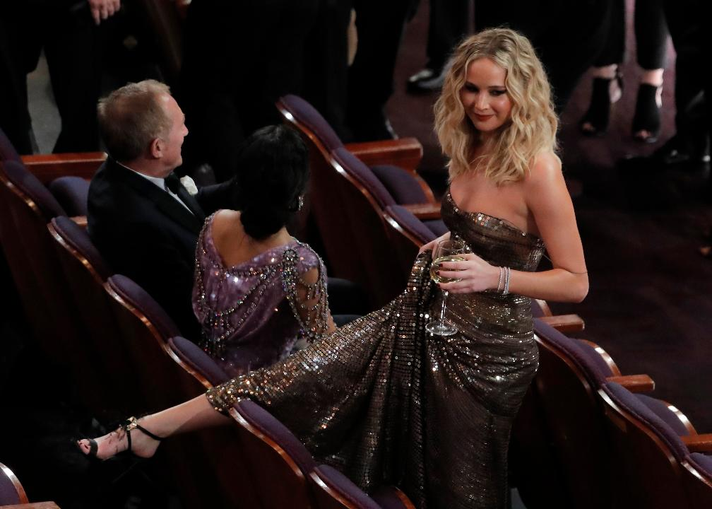 Academy Awards: Jennifer Lawrence juggles wine, climbs over chair