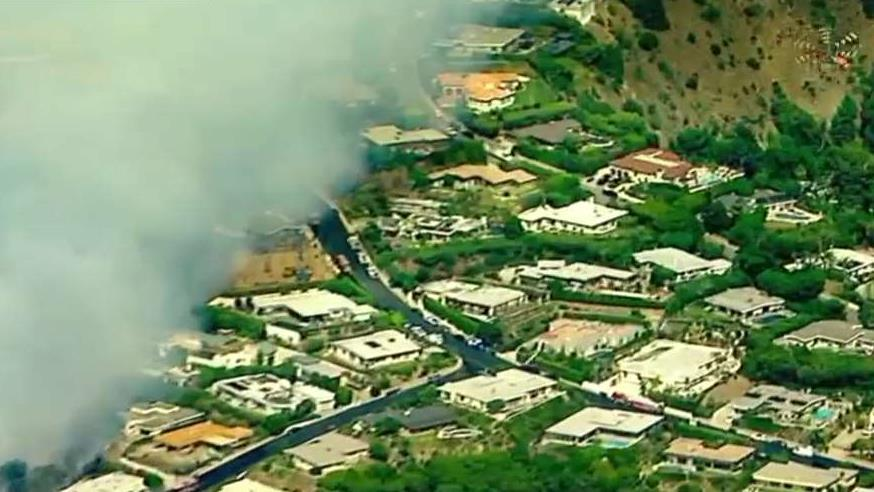 Air and ground crews fight the flames in Pacific Palisades.