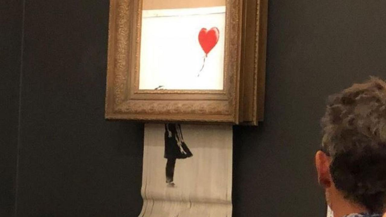 A Banksy stencil spray painting triples its auction estimate and becomes a record for the elusive artists. However, seconds after it was officially sold, the piece runs through a shredder hidden in the frame.
