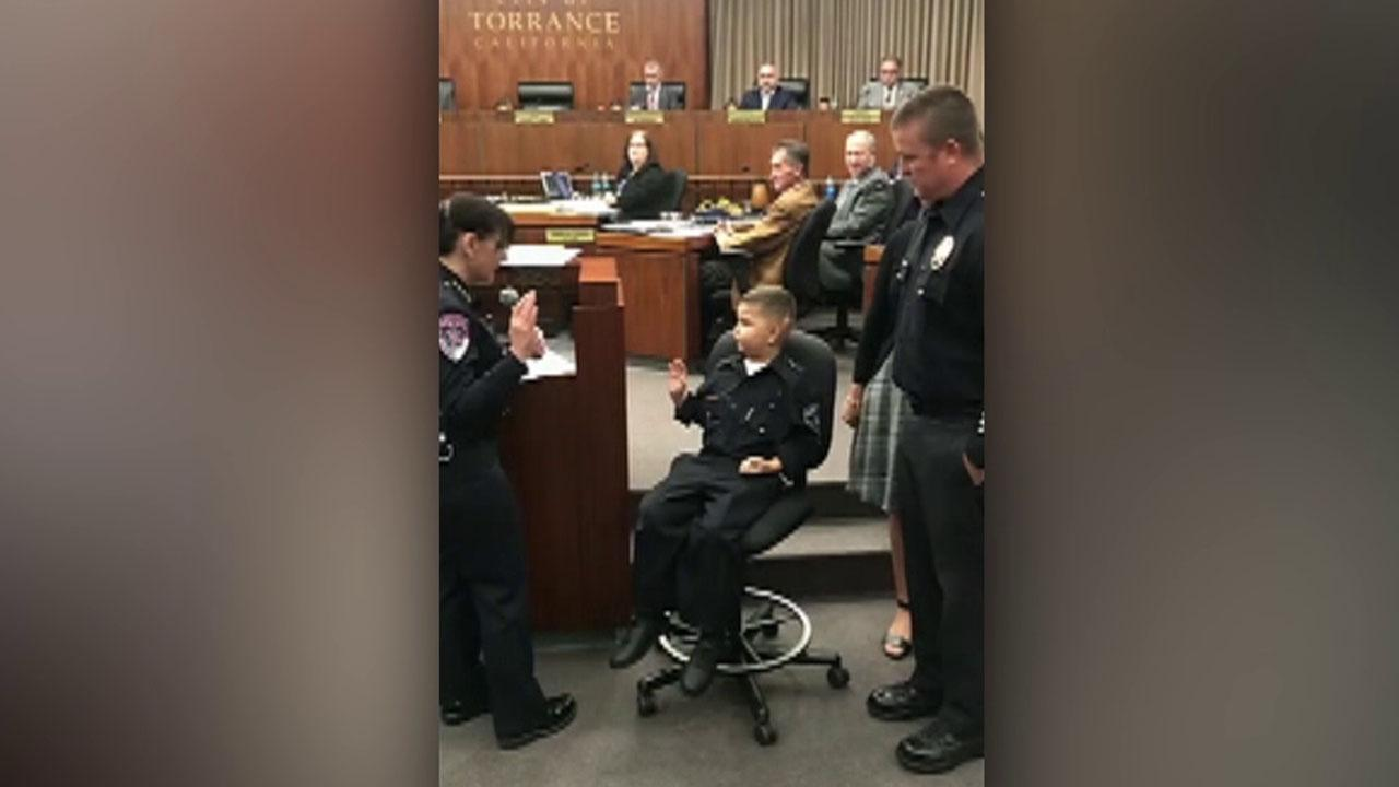Terminally ill California boy, 7, is sworn in as honorary cop, following in dad's footsteps