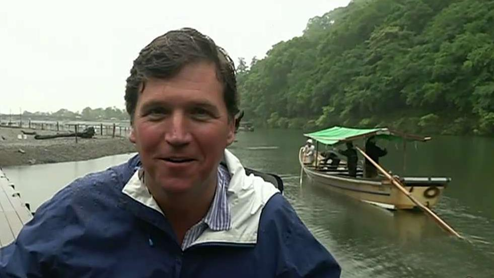 Tucker Carlson makes it back to land after a boat ride in Kyoto, Japan