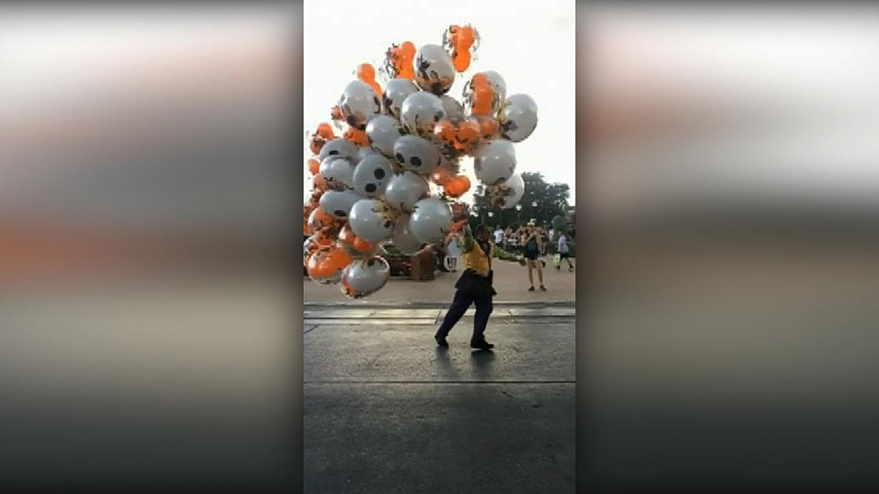 Walt Disney World employee nearly blown away by strong wind while carrying balloons, video shows